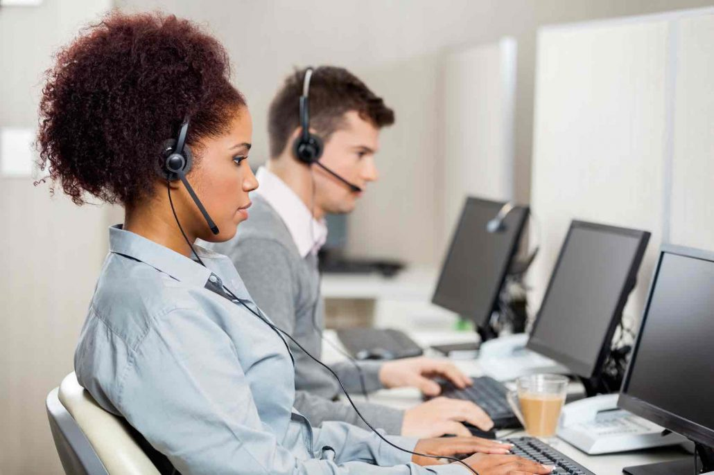 Side view of female customer service representatives with colleague working in call center