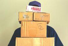 Joven con muchas cajas en sus brazos